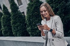 Planning the day. Beautiful young woman in suit using smart phone and smiling while standing outdoors royalty free stock photo