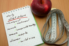 Planning of a diet. Measuring tape, apple and a notepad with a  daily diet plan Stock Image