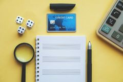 Planning expense for the future with credit card and calculate and note and dice for good luck stock photos