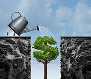 Planning For Financial Success. Business concept as a group of businesspeople using a watering can to feed a growing money tree that will close the gap and Stock Photos