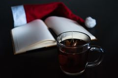 Planning future on Christmas concept: a notebook with blank pages, a black pen, Santa hat, glass mug with teabag, all on dark dini Stock Photography