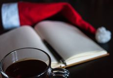 Planning future on Christmas concept: a notebook with blank pages, a black pen, Santa hat, glass mug with teabag, all on dark dini Royalty Free Stock Image
