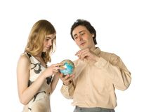 Planning holidays. A couple looking at a small globe Royalty Free Stock Images