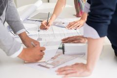 Planning interior of the house. Hands of designers planning interior of the house, selective focus Royalty Free Stock Image