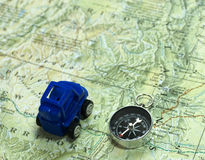 Planning the journey. Top view of toy car, map and compas to plan the journey Royalty Free Stock Photography