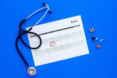 Planning medical examination concept. Regular medical examinations. Calendar with date circled, pills and stethoscope on. Blue background top view Stock Image