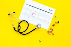 Planning medical examination concept. Regular medical examinations. Calendar with date circled, pills and stethoscope on. Planning medical examination concept Stock Photos