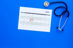 Planning medical examination concept. Regular medical examinations. Calendar with date circled and stethoscope on blue. Background top view royalty free stock photo