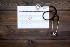 Planning medical examination concept. Regular medical examinations. Calendar with date circled and stethoscope on dark. Wooden background top view Royalty Free Stock Images