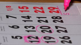 Planning meeting with sister on 29th day. Highlights making with pink marker on calendar page. 4K stock footage