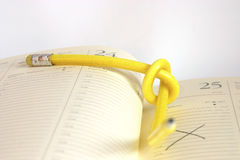 Planning my time - tough nut to crack. Yellow, twisted pencil on a diary Royalty Free Stock Photography