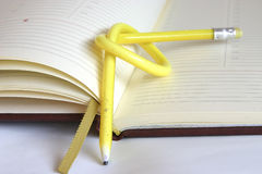 Planning my time - tough nut to crack. Yellow, twisted pencil on a diary Stock Photo