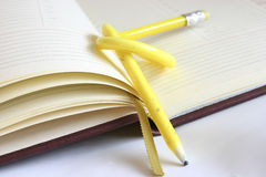 Planning my time - tough nut to crack. Yellow, twisted pencil on a diary Royalty Free Stock Image