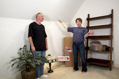 Planning New Home. Woman gestering to man with a paint brush standing among moving boxes in their new home Stock Photos