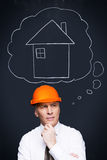 Planning new project. Thoughtful senior man in formalwear and hardhat holding hand on chin and looking away with a chalk drawn house upon his head Royalty Free Stock Photos