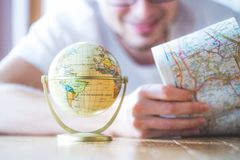 Planning the next journey: Man with map and miniature globe on the floor. Miniature globe model and a young man looking in a map. Prepare for travelling earth stock photography