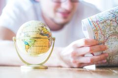 Planning the next journey: Man with map and miniature globe on the floor. Miniature globe model and a young man looking in a map. Prepare for travelling earth stock photo