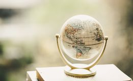 Planning the next journey: Miniature globe on a stack of books. Miniature globe model standing on a stack of books. Symbol for travelling earth transport journey stock photos