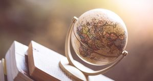 Planning the next journey: Miniature globe on a stack of books. Miniature globe model standing on a stack of books. Symbol for travelling earth transport journey stock images
