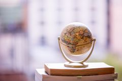Planning the next journey: Miniature globe on a stack of books. Miniature globe model standing on a stack of books. Symbol for travelling earth transport journey stock photography