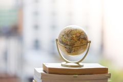 Planning the next journey: Miniature globe on a stack of books. Miniature globe model standing on a stack of books. Symbol for travelling earth transport journey royalty free stock photography