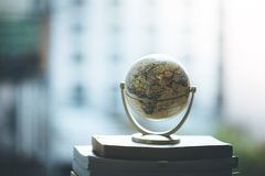 Planning the next journey: Miniature globe on a stack of books. Miniature globe model standing on a stack of books. Symbol for travelling earth transport journey royalty free stock photo