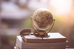Planning the next journey: Miniature globe and sunglasses on a stack of books. Miniature globe model and sunglasses lying on a stack of books. Symbol for royalty free stock photo