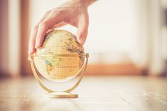 Planning the next journey: miniature globe on the wooden floor, hand touching it. Miniature globe model on the wooden floor, hand touching it. Symbol for royalty free stock photography