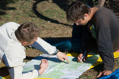Planning path. Hikers planning path on the map Stock Images