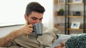Man writing to notebook and drinking coffee at home