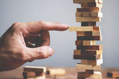 Planning, risk and strategy in business, businessman and enginee. R gambling placing wooden block on a tower Stock Photo