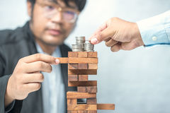 Planning, risk and strategy in business, businessman gambling. Placing wooden block on a tower Stock Images