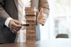 Planning, risk and strategy in business. Planning, risk and strategy in business, businessman gambling placing wooden block on a tower with vintage tone and Royalty Free Stock Image