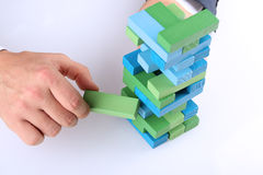 Planning, risk and strategy in business, businessman getting out a wooden block from a tower Stock Photography