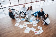 Planning strategy together. Business team looking at papers on floor with manager pointing to one idea. Cooperation. Corporate achievement. Planning design draw royalty free stock photos