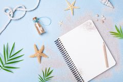 Planning summer holidays, tourism and vacation background. Travelers notebook with accessories on blue pastel table top view. stock photography