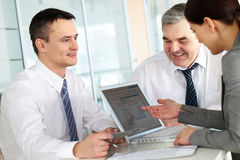 Planning team. A business team of three sitting at table and planning work Royalty Free Stock Photo