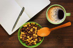 Planning th day during the breakfast. Planning the day or educating while having healthy breakfast of two varieties corn cereals and fresh coffee royalty free stock image