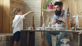 Planning their trip. Looking for adventure. Man and little child with binocular and miniature architecture. Boy son and. Father with world landmark buildings in stock video