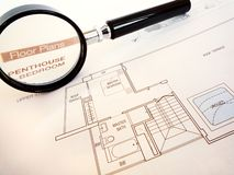 Planning to buy luxury penthouse home. A photograph image of a magnifier magnifying glass focused on the words floor plans and Penthouse, over the architectural Royalty Free Stock Photo