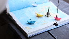 Planning a tour or travel destination idea. Paper boats on the map and the Eiffel Tower. stock video footage
