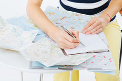 Planning a trip. Using maps and taking notes for the itinerary royalty free stock image