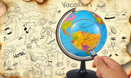 Planning For Vacation Destination. Photo image of a hand holding magnifying glass looking on earth globe, planning for vacation travel trip destination concept Stock Photography