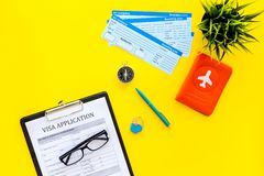 Planning a vacation, planning a trip. Visa application form near passport and airplane ticket on yellow background top royalty free stock images