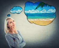 Planning vacation. Portrait of thoughtful woman looking up and imagining a holiday at the sea beach. Dreaming of vacation with a positive face expression stock photo
