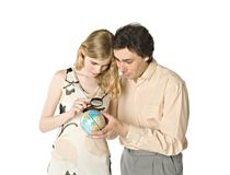 Planning vacations together. A couple looking at a small globe through a magnifier Stock Photo