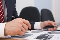 Planning work. Image of male hand with pen over documents while planning work Royalty Free Stock Image