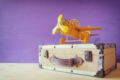 Plano amarelo do brinquedo do vintage e mala de viagem velha imagem de stock royalty free
