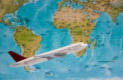 Plano branco do brinquedo no fundo do mapa do mundo foto de stock