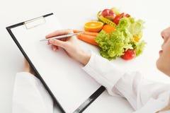 Plano da dieta da escrita do doutor do nutricionista na tabela foto de stock royalty free